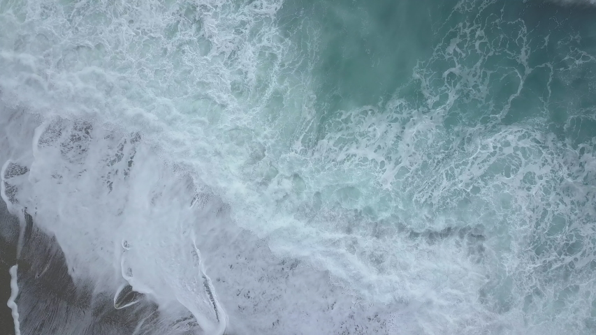 Aerial top view of sea waves foaming and splashing, big waves from above rolling and breaking on empty ocean beach. Zoom in drone shot | Shutterstock HD Video #1031746262