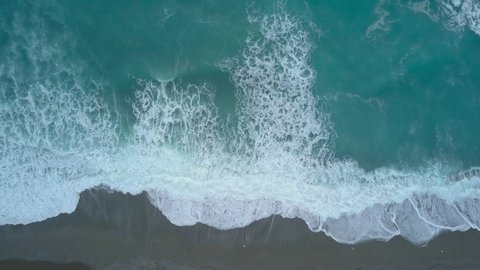 Aerial top view turquoise sea waves break on empty sand beach. Clean sea waves from bird's eye view, ocean waves reaching shore and splashing from above