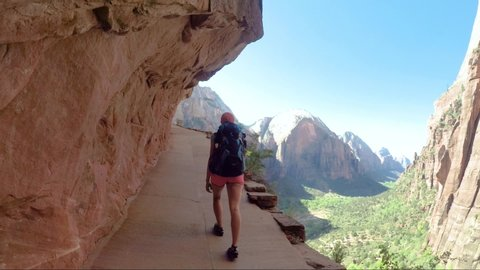 Young woman wearing backpack is walking to Angel's Landing in Zion National park in Utah, USA. Female on a hiking trail in Zion National Park in Usa