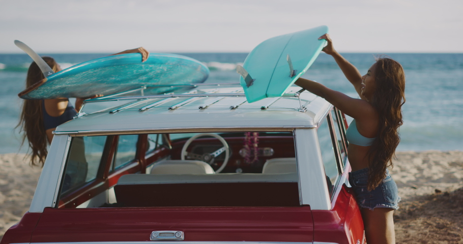 Young attractive women at the beach with vintage beach cruiser car, getting ready to surf at sunset, island beach lifestyle | Shutterstock HD Video #1031878352