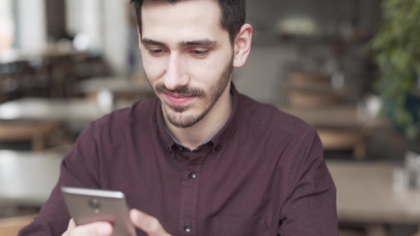 Smiling man sends a text message on his phone in a café. #1031887502