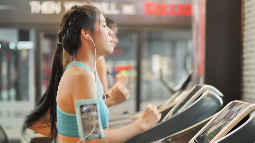 Young beautiful woman asian with friend running on a treadmill at gym. Fitness and healthy lifestyle concept. Slow motion | Shutterstock HD Video #1031891552