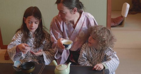 Mother and two children wearing traditional yukata eat from a bowl and drink tea at a chabudai, a low Japanese table, on a tatami mat floor in a Ryokan in Japan