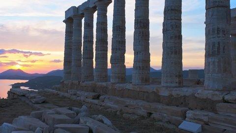 Greece Cape Sounio. Ruins of an ancient temple of Poseidon, Greek god of the sea, on sunset. Pan shot of temple ruins on sunset. Tourist landmark of Attica, Sounion, Greece