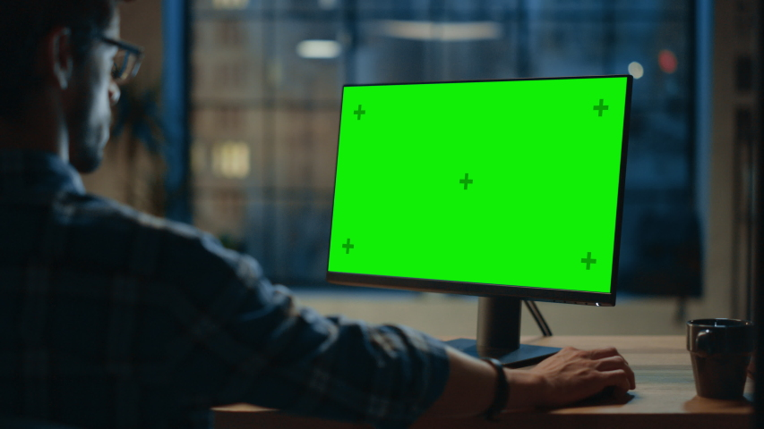 Over the Shoulder: Creative Young Man Sitting at His Desk Using Desktop Computer with Mock-up Green Screen. Evening in the Stylish Office Studio with City Window View | Shutterstock HD Video #1031975672