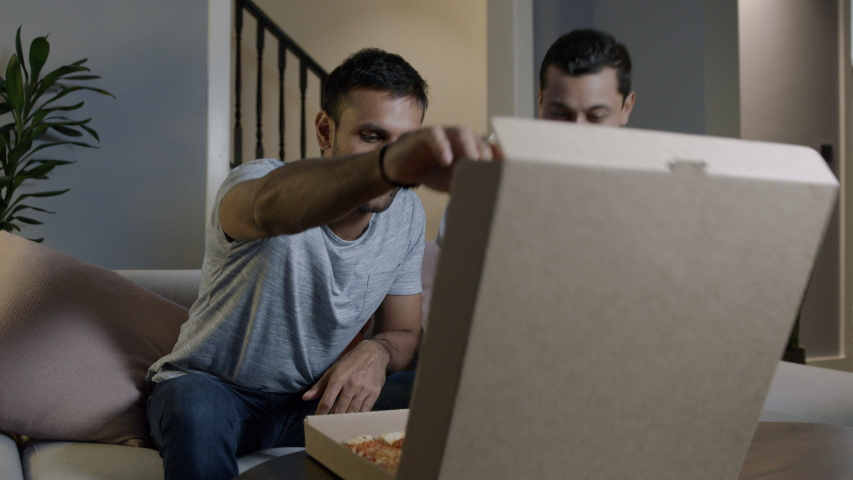 Two young men receive delivery of takeaway pizza. They open the box, take a slice and watch tv. | Shutterstock HD Video #1031979812