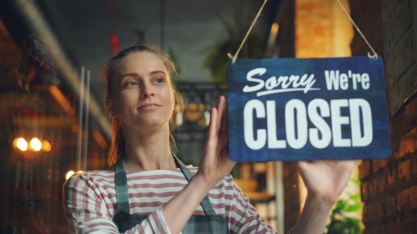 Shopkeeper in apron hanging sorry we are closed sign on front door smiling looking outside informing people of workday end. Cafe, people and business concept. | Shutterstock HD Video #1031982032