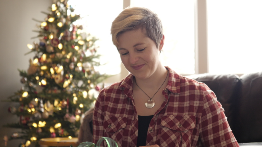 Edgy young blonde woman's face lights up as she opens a gift with Christmas tree in background.   Shutterstock HD Video #1031991182