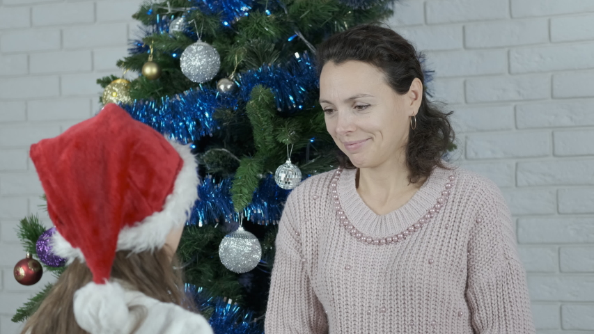 Child giving a present. Christmas tree on the background.   Shutterstock HD Video #1032010952