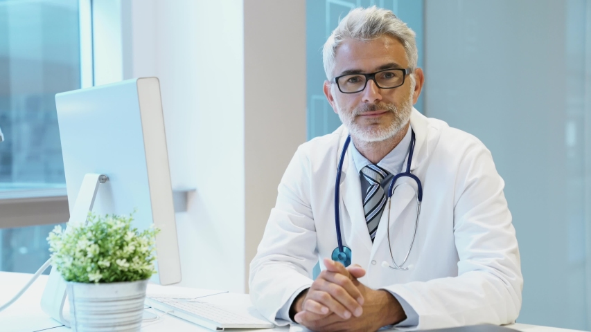 Mature doctor sitting at desk looking at camera | Shutterstock HD Video #1032056852