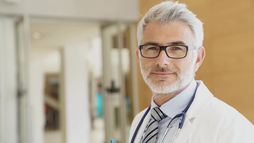 Close up of mature doctor standing in hospital hallway | Shutterstock HD Video #1032057002