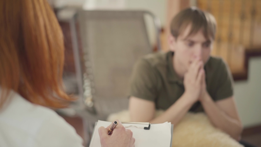 Young man sitting in the office of psychologist, telling her about his problems. Red-haired female psychologist consulting her patient | Shutterstock HD Video #1032078662