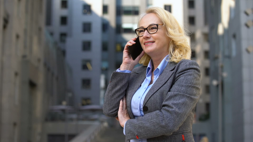 Cheerful female manager talking on phone standing outside, client communication | Shutterstock HD Video #1032111302