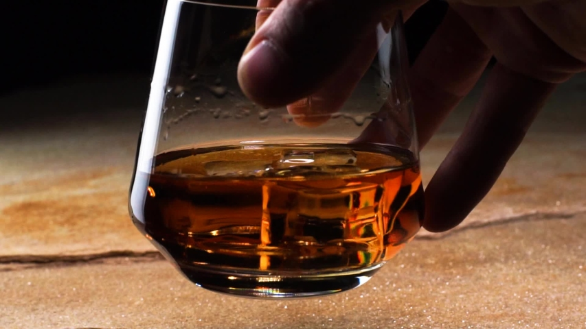 Close up Slow Motion Hand Holding A Glass Goblet With Whiskey And Ice And Swinging It Over The Stone Tabletop And Black Background. Concept Of Fine Alcoholic Drinks Alcoholism And Tasting Drinks | Shutterstock HD Video #1032142862