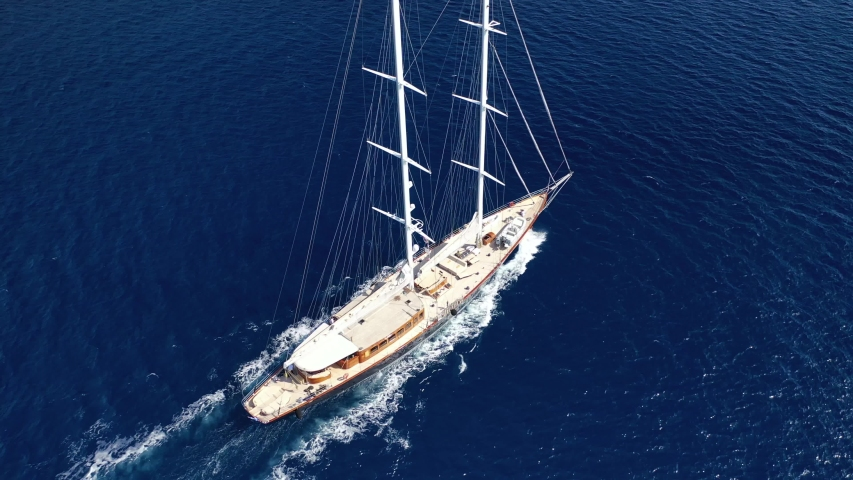 Aerial view tracking video of yacht sailing on deep blue open sea at sunny day | Shutterstock HD Video #1032159572