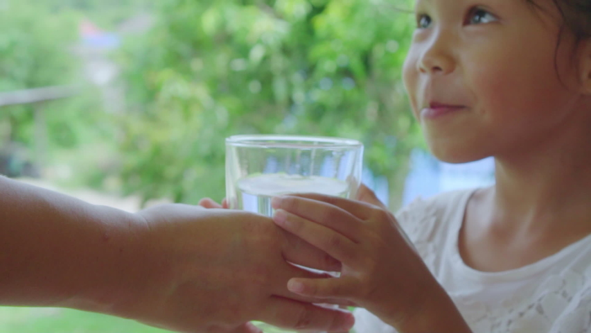 Close up shot of clean pure water glass while mother holding and gives to daughter drink in garden background, slow motion