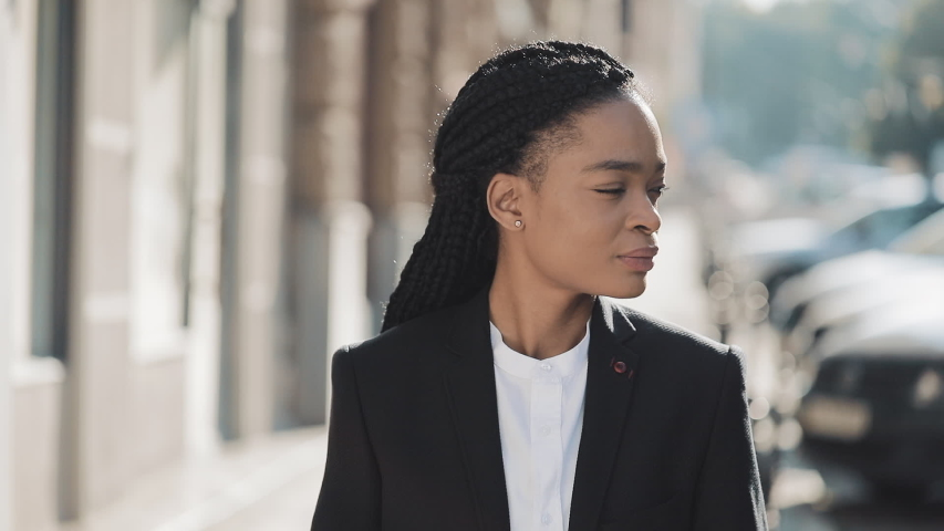 Portrait of stylish afro business woman standing on the old street background. She looking at the camera and smiling. She listen music in wireless earphones. Black Stylish. Dreadlocks. Afro Hairstyle. #1032183902