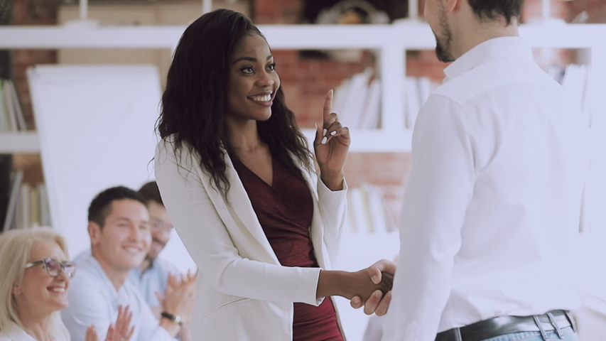 Smiling black female employee get rewarded handshake caucasian boss, helpful manager shake hand of successful african business woman congratulate promote, appreciation recognition at work concept