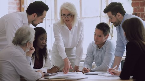 Diverse business team and old woman mentor leader brainstorm on paperwork talk engaged in teamwork at corporate briefing, senior boss explain new project plan training staff people at group meeting