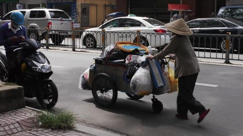 Ho Chi Minh, Vietnam - 06 04 2019: Poor elder woman wearing a coolie hat pushing a cart full of junk in the middle of a city