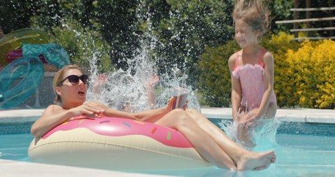 funny children jumping in swimming pool splashing mother relaxing on swim tube kids playfully surprise mom family having fun on sunny day enjoying summer 4k