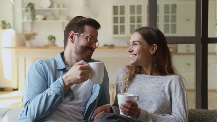 Happy young family couple relaxing talking laughing holding cups drinking coffee tea sitting on sofa together in living room, loving husband and wife bonding enjoying pleasant conversation at home