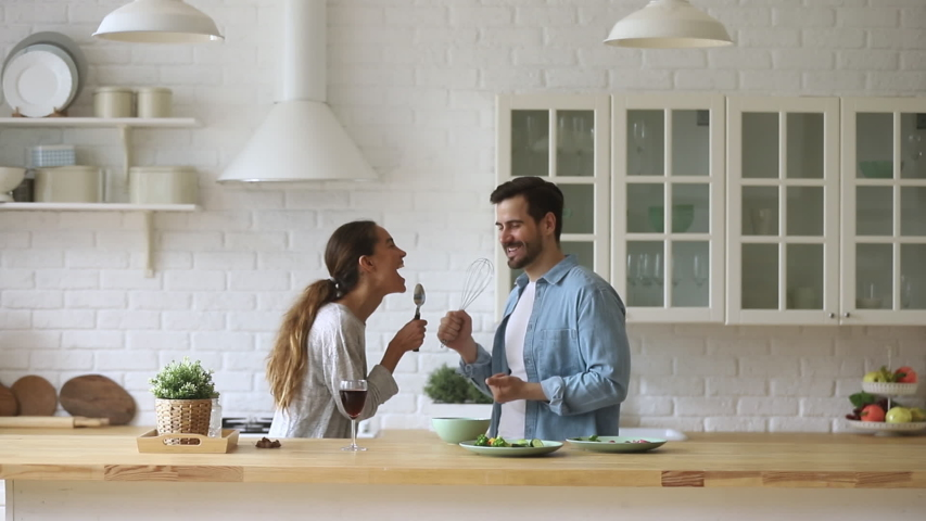 Funny young couple laughing holding kitchenware singing song together dancing to music enjoying cooking in modern cozy kitchen, happy carefree husband and wife having fun preparing food at home | Shutterstock HD Video #1032517202