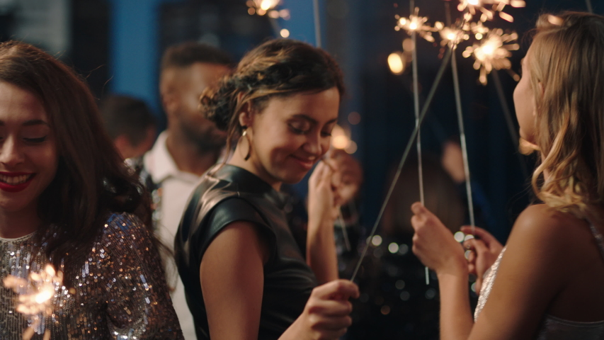 Group of friends celebrating with sparklers dancing enjoying glamorous new years eve party having fun holiday celebration wearing stylish fashion at social gathering on rooftop at night | Shutterstock HD Video #1032521252