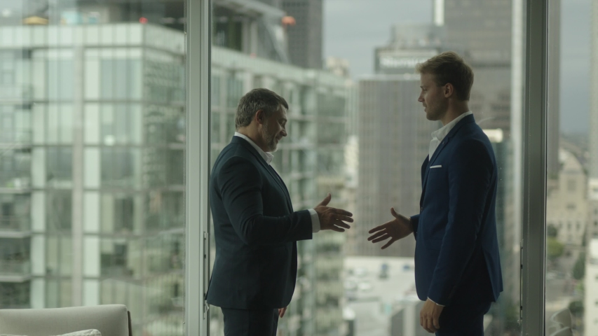 Two business partners do handshake in front of view on downtown and skyscrapers. A good business deal. | Shutterstock HD Video #1032524282