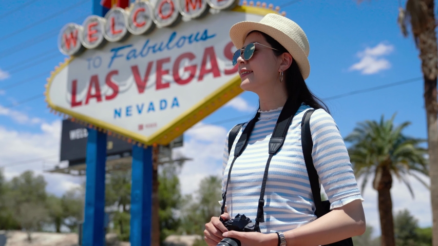 Happy young asian woman visitor standing near Las Vegas Welcome sign. Beautiful girl travel photographer smiling with Las Vegas billboard on background. female tourist with camera trip in Nevada USA | Shutterstock HD Video #1032569192