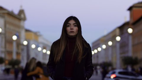 Close up portrait of attractive, fashionable, and serious brunette  woman with long hair confidently walking in St Peter's Square in the Vatican