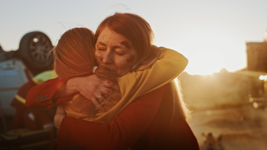 Injured Mother and Young Daughter Reunite After Terrible Car Crash Traffic Accident, They Hug Happily. In the Background Through Smoke and Fire, Courageous Paramedics and Firefighters Save Lives | Shutterstock HD Video #1032836312