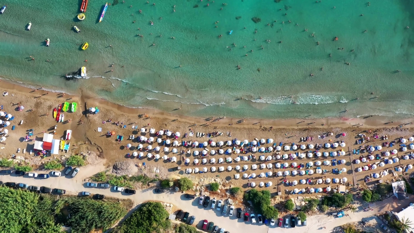 Aerial view of Coral Bay beach with umbrellas, swimming people in transparent sea water. Pegeia, Paphos District, Cyprus   Shutterstock HD Video #1032858542