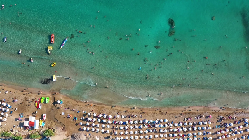 Aerial view of Coral Bay beach with umbrellas, swimming people in transparent sea water. Pegeia, Paphos District, Cyprus | Shutterstock HD Video #1032858542