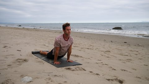 A man doing relaxing yoga poses on the beach to destress with ocean waves on the California shore in slow motion.
