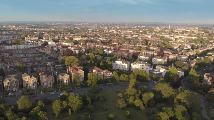 Aerial flyover green tree lined city streets of Bristol, England, drone shot at sunset golden hour | Shutterstock HD Video #1032887012
