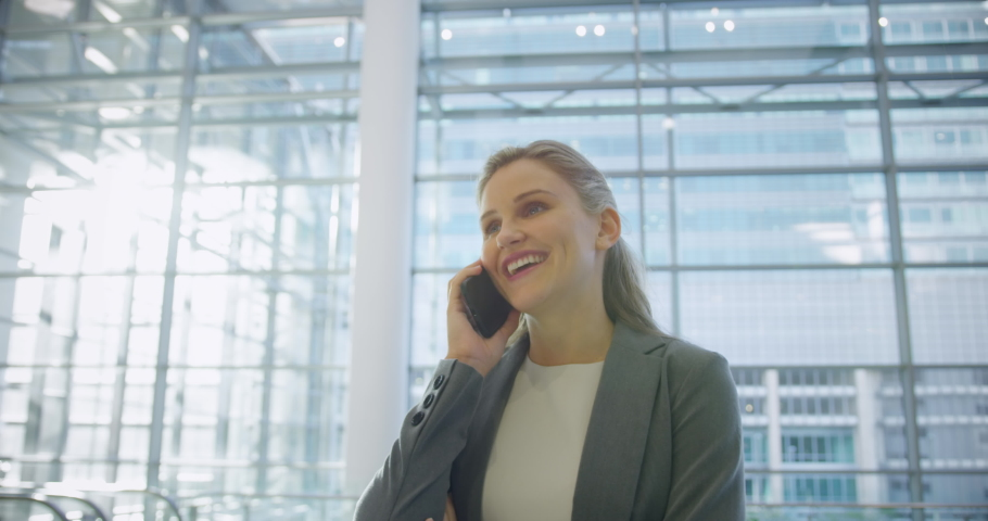 Front view of Businesswoman talking on mobile phone in the lobby at office. She is smiling 4k   Shutterstock HD Video #1032897992