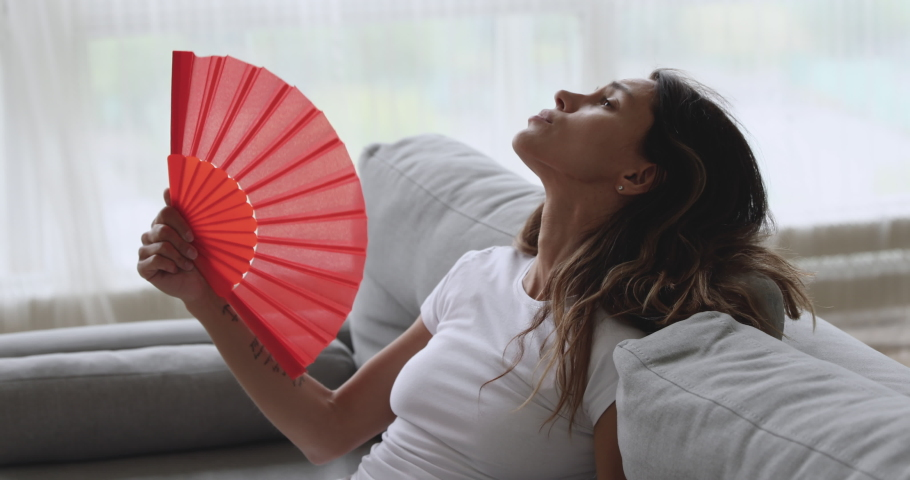 Overheated unhappy young woman feeling hot waving fan annoyed with high temperature sit on couch at home, stressed sweaty girl sweating suffer from summer weather heat problem without air conditioner | Shutterstock HD Video #1032911132
