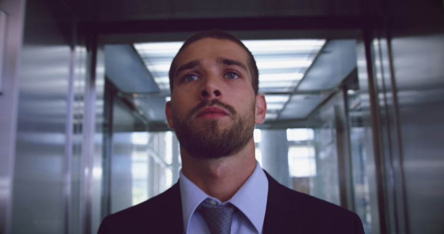Front view of Caucasian Businessman getting out of elevator at modern office. He is looking away 4k