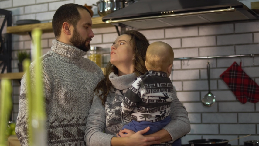 Bearded father in warm sweater playing with baby little son who is in mother arms in the kitchen. Woman gives child to father and take him back. Happy friendly family spend time together | Shutterstock HD Video #1033023272
