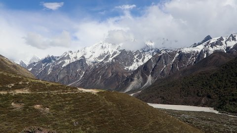 Tripod shot of fasting clouds in Langtang Valley with the ginormous Himlayan snowcapped mountains in the background