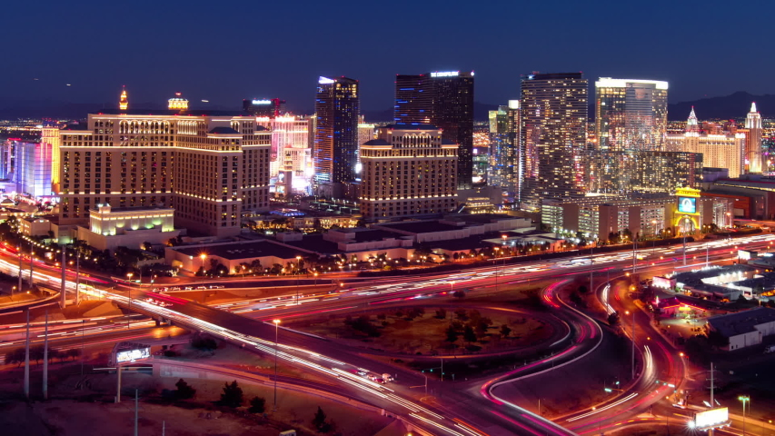 Zoom out, panning shot of the Las Vegas skyline and freeway transition from day to night. | Shutterstock HD Video #1033063082