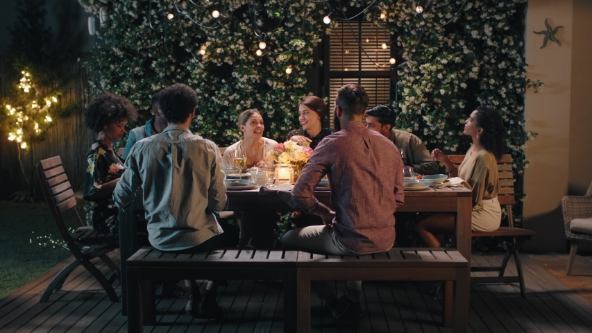 Dinner party friends celebrating evening together sharing homemade meal enjoying casual conversation having fun weekend reunion relaxing on calm summer night outdoors 4k footage