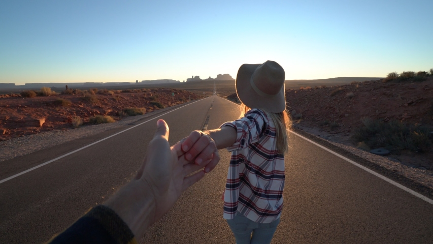 Follow me to concept; young woman leading boyfriend on empty highway in USA at sunset; Couple holding hands following each other near Monument Valley    Shutterstock HD Video #1033112762