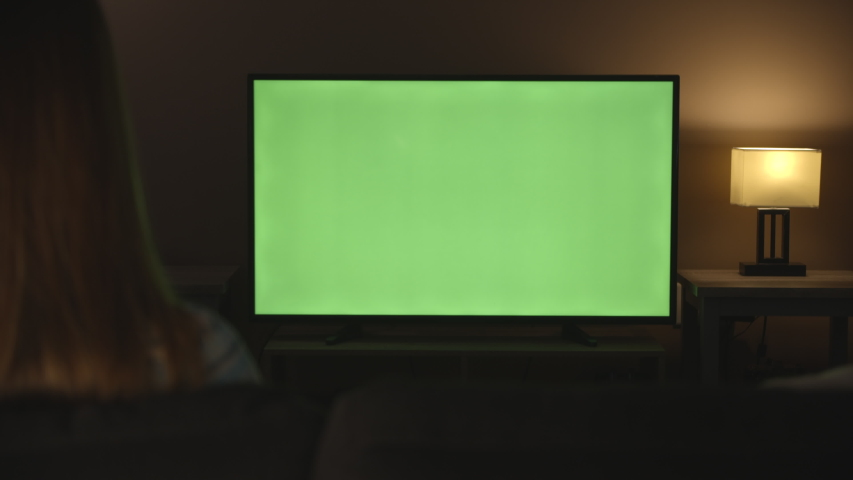 Woman watching Green Screen TV and changing channels in evening, 4k #1033239272