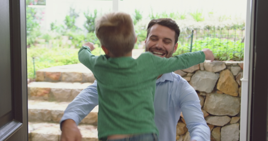 Rear view of Caucasian boy opening the door and embracing his father in a comfortable home. They are smiling 4k #1033261172