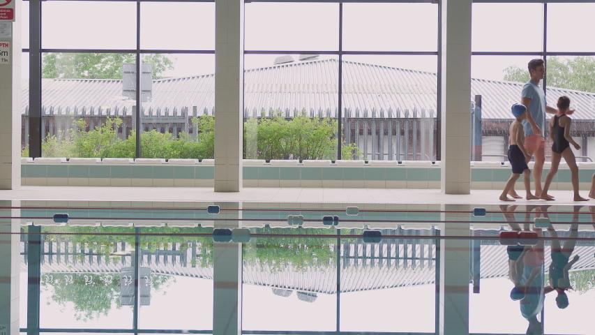 Male Coach Walks Children In Swimming Class Along Edge Of Indoor Pool | Shutterstock HD Video #1033265252