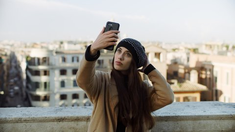 Fashionable Italian woman taking selfies with her phone on balcony overlooking buildings and churches of Rome. 4k RED camera.