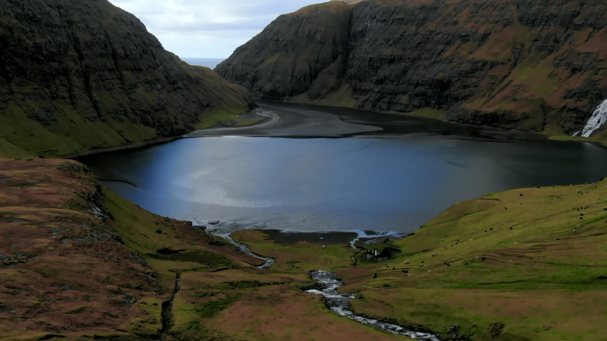 Aerial Sloping Valley and Farm Animals By lake with Rocky Cliffs in Distance, Streymoy Island, Faroe Islands | Shutterstock HD Video #1033296902