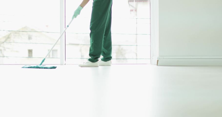 """Blurred view of professional cleaner and safety sign """"WET FLOOR"""" indoors  